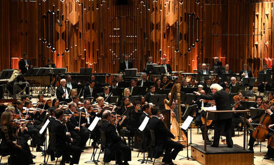 Photo of Sir Simon Rattle conducting the London Symphony Orchestra in the Barbican Hall