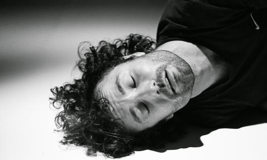 Man rests head on floor in black and white
