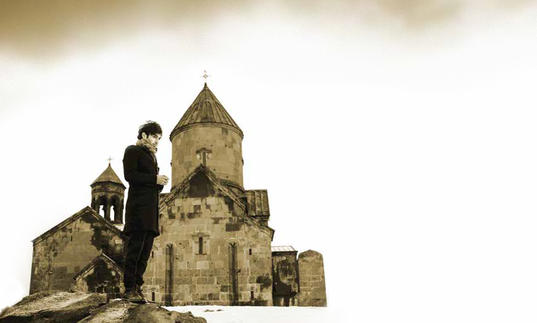 Tigran Hamasyan standing in front of an imposing castle in his native Armenia