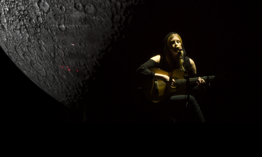 Susanne playing guitar next to a projection of a giant moon