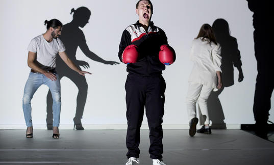 three people on a stage, one wears boxing gloves and screams