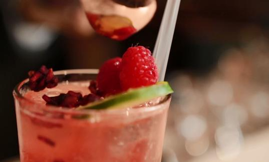 close up of a pink cocktail with raspberries