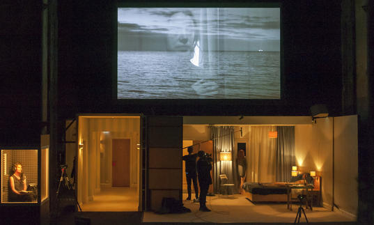 A screen on the top half of the image showing a woman's face and the sea. Below is a woman in a bedroom film set and a narrator in a recording box.
