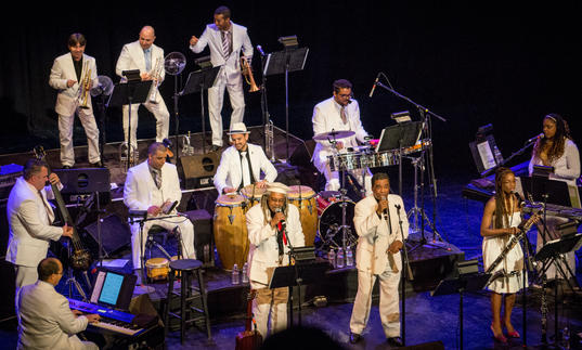 Afro-Cuban All Stars playing music all dressed in white suits