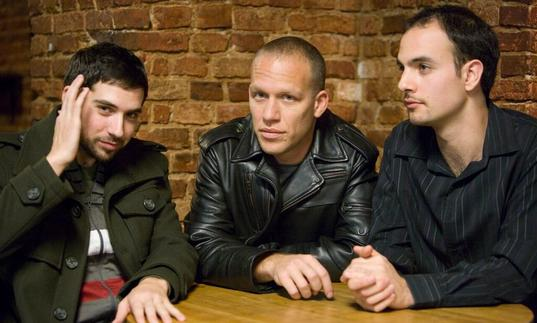 The Avishai Cohen trio wearing dark jackets sitting at a wooden table