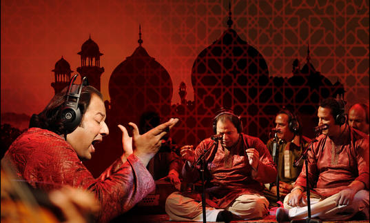 Rizwan-Muazzam Qawwali perform tradition instruments and sing seated with a backdrop of a mosque