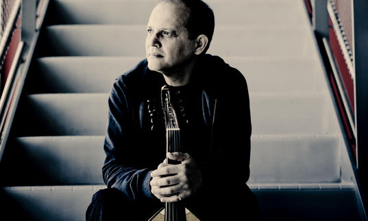 Anouar Brahem sitting on a staircase holding his oud