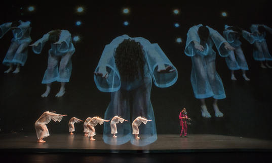 A group of dancers with video in the background