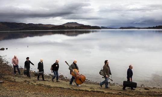 Transatlantic Session musicians walking along a loch