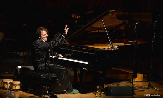 Chilly Gonzales is playing a piano one handed whilst doing a wave