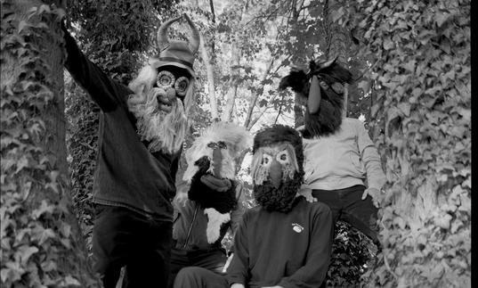 Four performers wearing masks pose in a tree