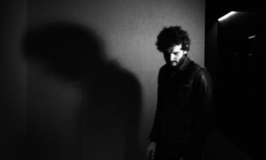 A black and white photo of Apparat in front of a wall, his shadow is cast on the wall behind him