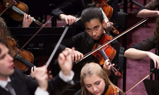 A member of the National Youth Orchestra of Great Britain playing violin or viola very intensely
