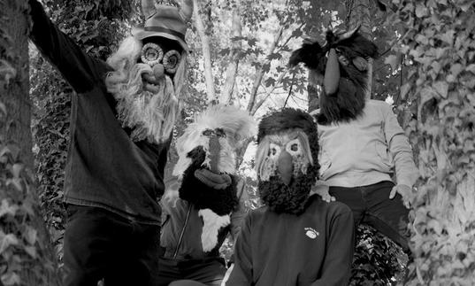 Pantha Du Prince and his collaborators in a tree wearing masks