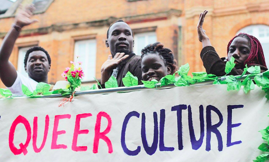 a group of people stand on a stage with a banner saying queer culture on it
