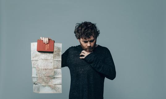 Gabriel Kahane holds up a book and map of North America