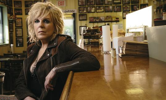 Lucinda Williams leaning one arm on the counter at a diner