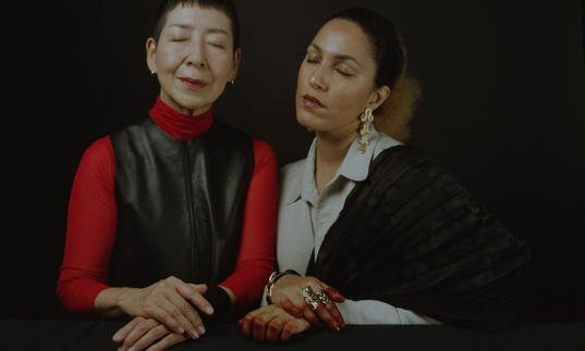 Midori Takada and Lafawndah sit side by side with their eyes closed