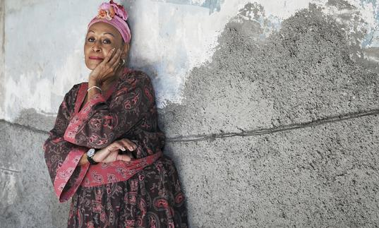 Omara Portuondo in front of a painting of the Cuban flag