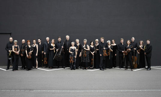 Freiburg Baroque Orchestra standing black wall