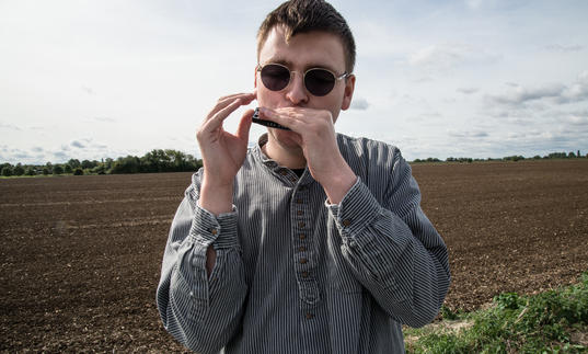 Oliver Cross playing his harmonica in a field