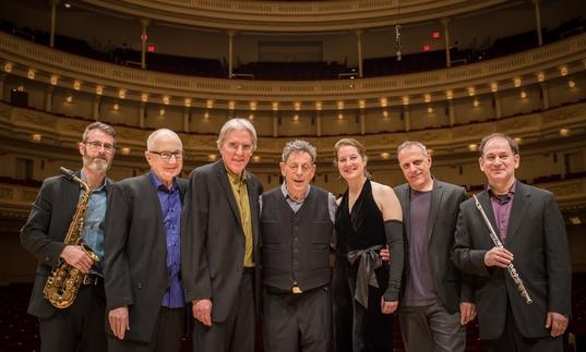The Philip Glass Ensemble with Philip Glass pose for a photo in a concert hall
