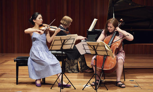 Piano trio performing on stage