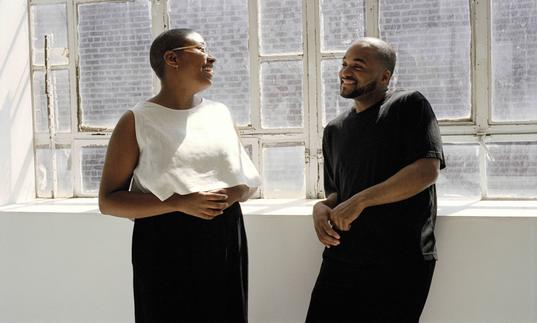 Cecile McLorin Salvant and Sullivan Fortner leaning on a ledge in front of windows with sun streaming in