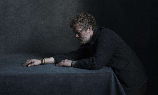 Glen Hansard stretching his right arm across a table. He is wearing leather bracelets.