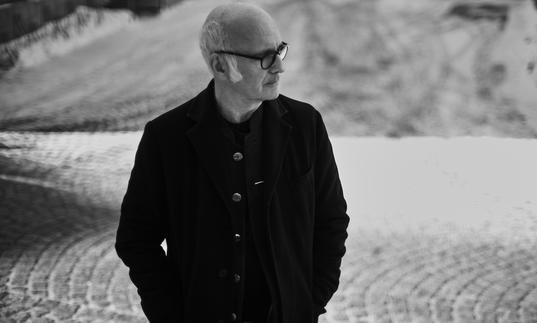 Ludovico Einaudi standing outside with his hands in his pockets, looking to his left.