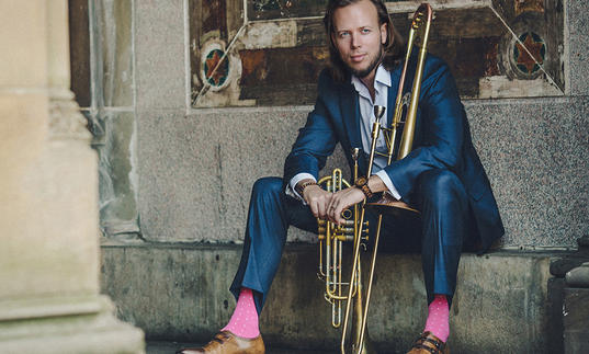 Jazz trombonist Elliot Mason sitting down in blue suit