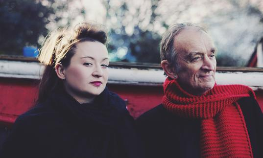 Eliza and Martin Carthy sitting in a boat outdoors. Eliza is looking at the camera and Martin is wearing a red scarf.