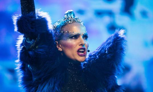 A bejewelled Natalie Portman in a fur jacket performing in a stadium