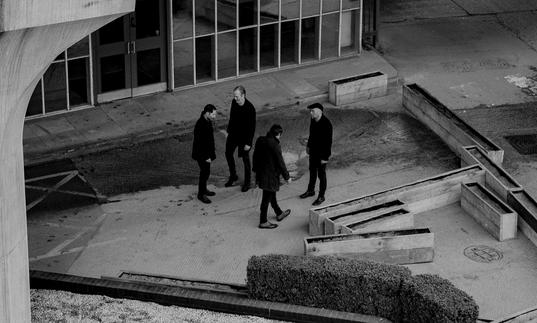 Ride standing in a group, in the surrounds of a brutalist building