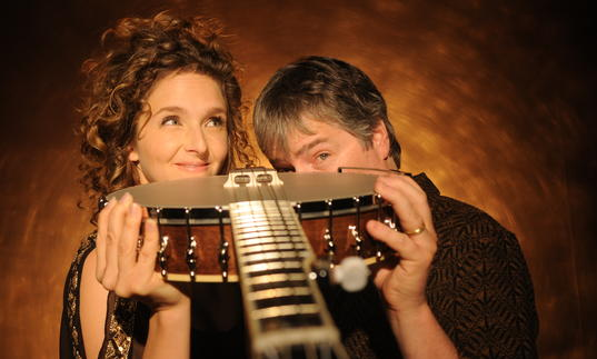 Bela Fleck and Abigail Washburn playfully pointing a banjo at the camera