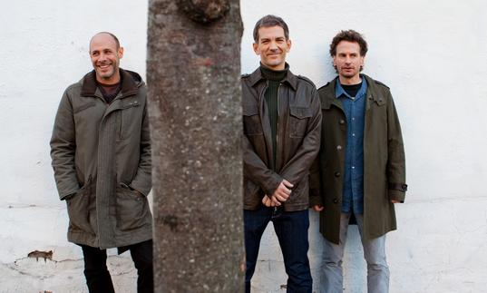 The Brad Mehldau Trio standing against a white brick wall, with a tree in front of them