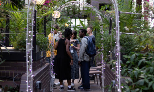 A group of people standing under an arch in conservatory