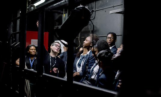 A group of school students backstage at the Barbican Theatre