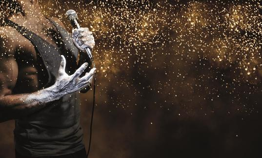 Gold image with a man in black vest top holding a microphone and throwing glitter.