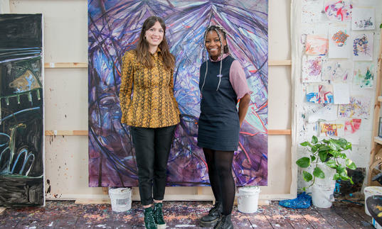 Two women standing in front of a purple painting