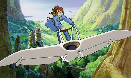 young boy riding on the back of a wind glider contraption