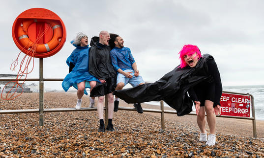 4 people in anoraks are on a windy beach. One has a bright pink wig.