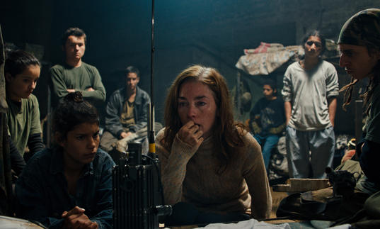 A young woman and some children wait attentively at a radio in the film Monos