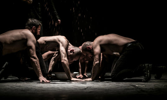four topless men in a dark room appear to be eating from the floor