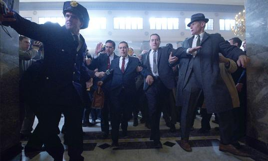 Al Pacino and Robert De Niro are escorted through a lobby by police in Martin Scorsese's The Irishman