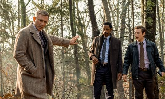 Daniel Craig in a cream overcoat stands in the woods with Lakeith Stanfield, in Rian Johnson's Knives Out