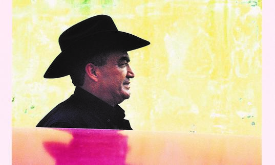 Eliades Ochoa in profile, wearing a black wide-brimmed hat, standing next to a yellow wall