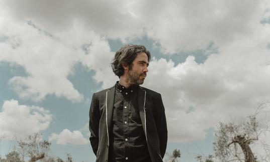 Patrick Watson wearing a black shirt and black jacket looking over his left shoulder, the sky behind him is cloudy
