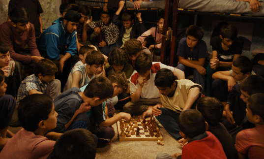 A large group of young boys play chess in The Orphanage