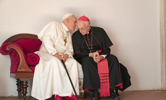 the two popes, Francis and Benedict sit next to each other with one whispering in the other's ear